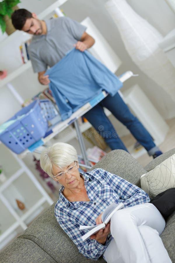 Męski opiekun pracuje za leżanką z starszą czytelniczą książką obrazy stock