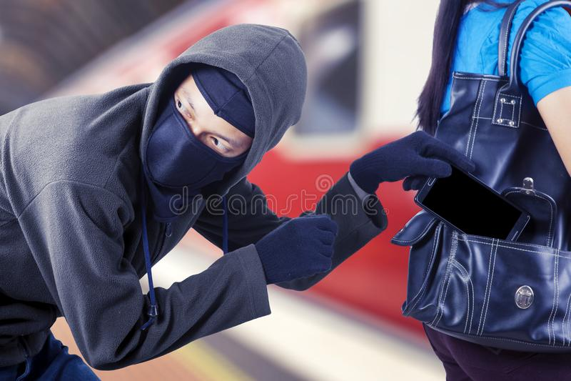 Męski pańszczyźniany kraść smartphone od jego ofiary zdjęcia royalty free