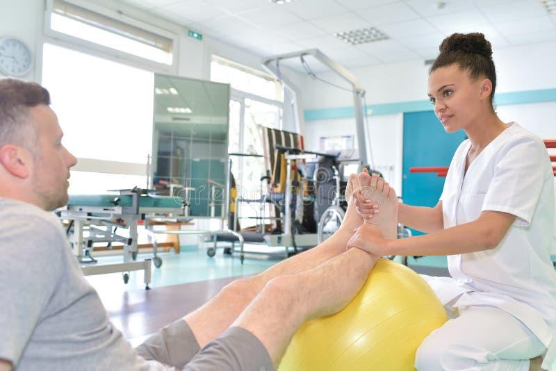 Męski pacjent podczas fizycznej terapii praxis i kobiety physiotherapist obrazy stock