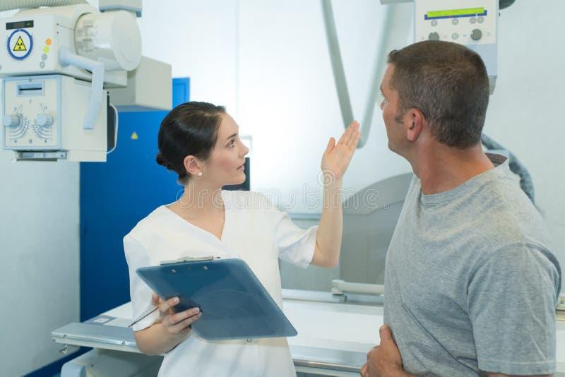 Męski pacjent przy xray maszyną z kobiety lekarką obrazy royalty free
