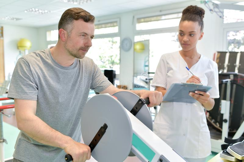 Męski pacjent z żeńskiego physio terapeuta pracującymi out rękami obraz stock