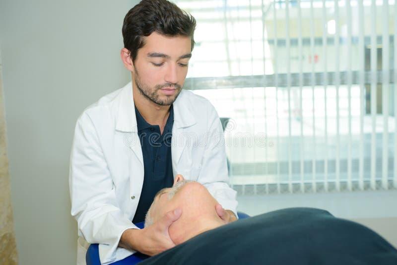 Męski physiotherapist daje kierowniczemu masażowi starszego pacjenta w klinice obrazy royalty free