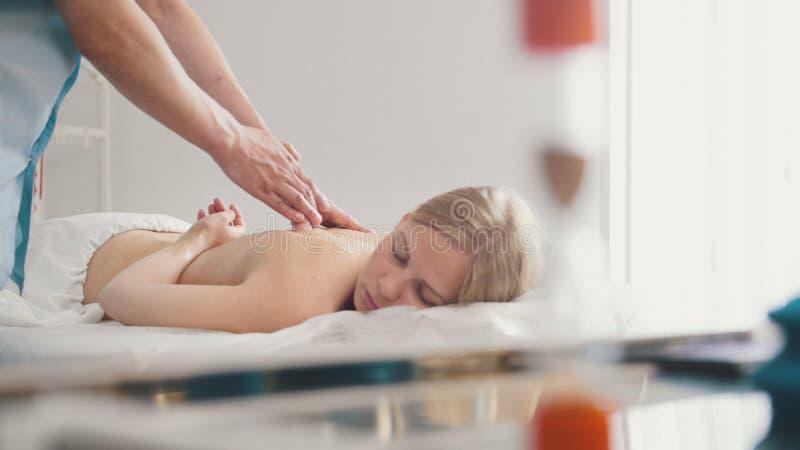 Męski physiotherapist masowania kobiety ` s plecy w medycznym biurze zdjęcie stock