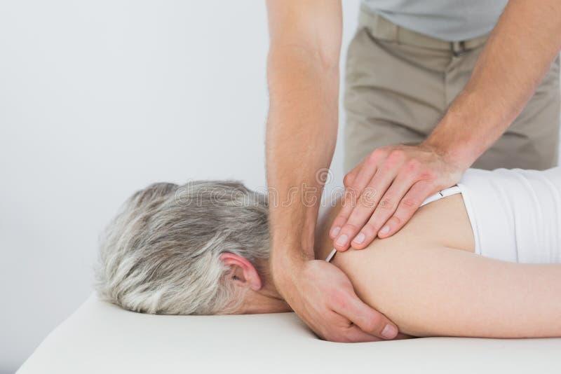 Męski physiotherapist masuje kobiety starszego ramię obrazy royalty free
