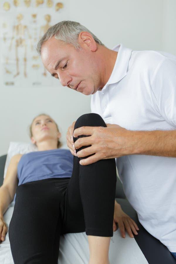 Męski physiotherapist z pacjentami iść na piechotę w physio pokoju obrazy stock
