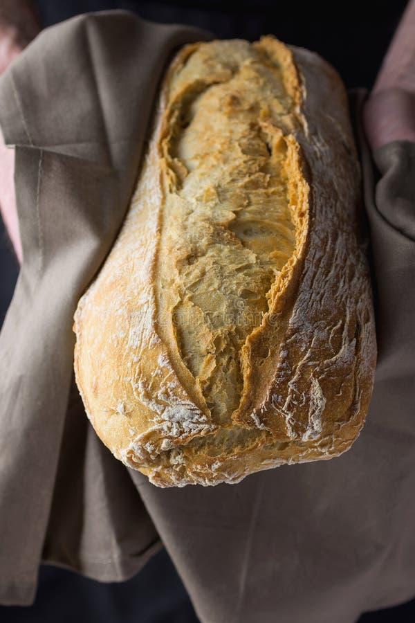 Męski Piekarniany mienie w rękach w Popielatym Bieliźnianym ręcznika Świeżo Piec ręka Wykonującym ręcznie Nieociosanym Chlebowym  zdjęcia stock