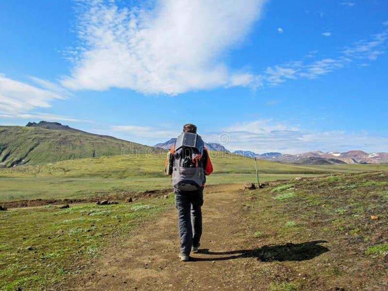Męski podróżnik od plecy w górach z dużym panelem słonecznym i plecakiem obraz stock