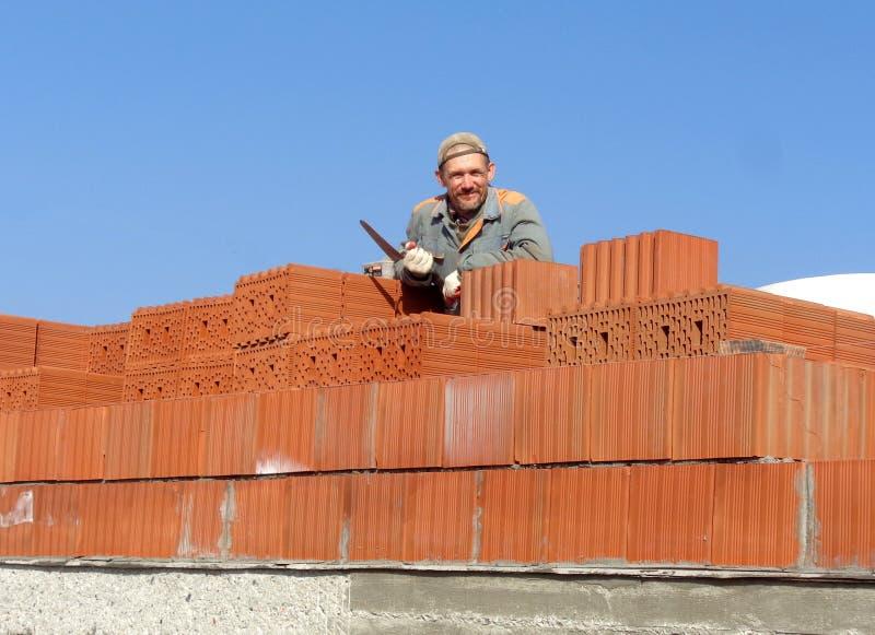 Męski pracownik budowlany przy budowa ceglanego domu mienia narzędzia ono uśmiecha się rozochocony fotografia royalty free