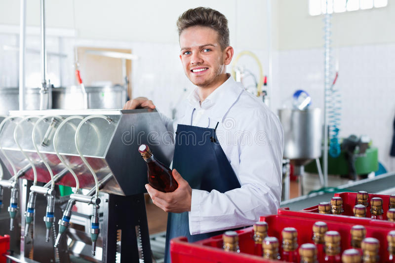 Męski pracownik pakuje wino butelki przy iskrzastego wina fabryką obraz royalty free