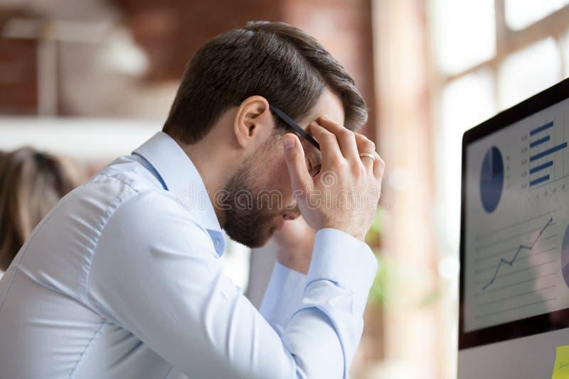 Męski pracownik siedzi w biurowym cierpieniu od silnej migreny obrazy royalty free
