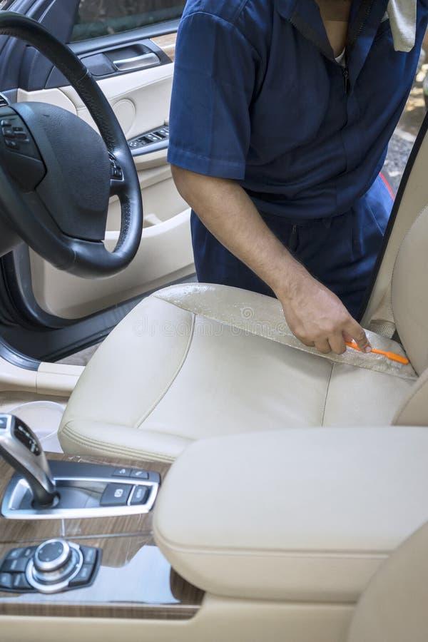 Męski pracownik szoruje samochodowego siedzenia obraz stock
