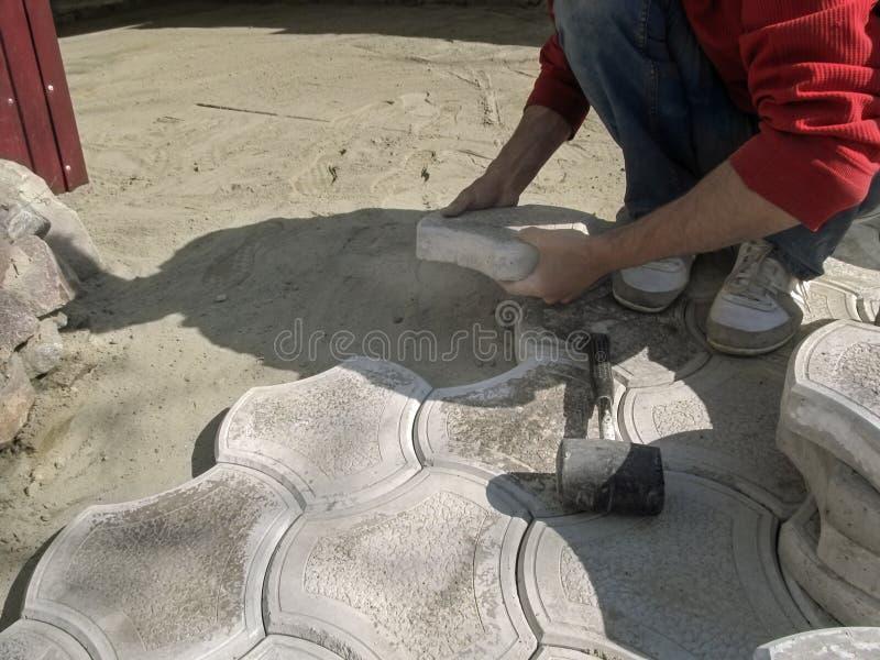 Męski pracownik trzyma betonowego bruku płytkę i gumowy dobniak kłama w pobliżu Pojęcie praca na kłaść obliczający dekoracyjnego zdjęcia royalty free