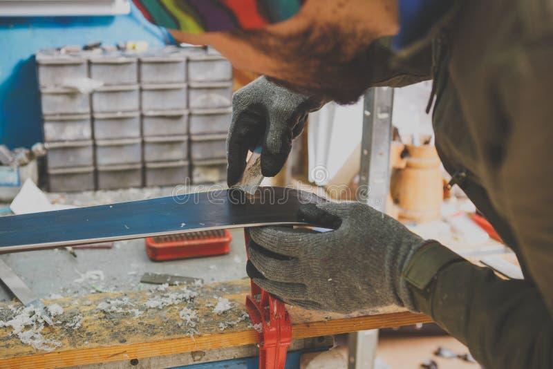 Męski pracownik w narciarskim usługowym warsztacie naprawia ślizgową powierzchnię narty Zakończenie ręka z plastikowym scrapper d zdjęcie stock