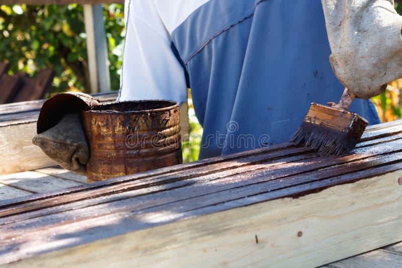 Męski pracownik w starej rękawiczce maluje deski dla domowej dekoracji zdjęcie stock