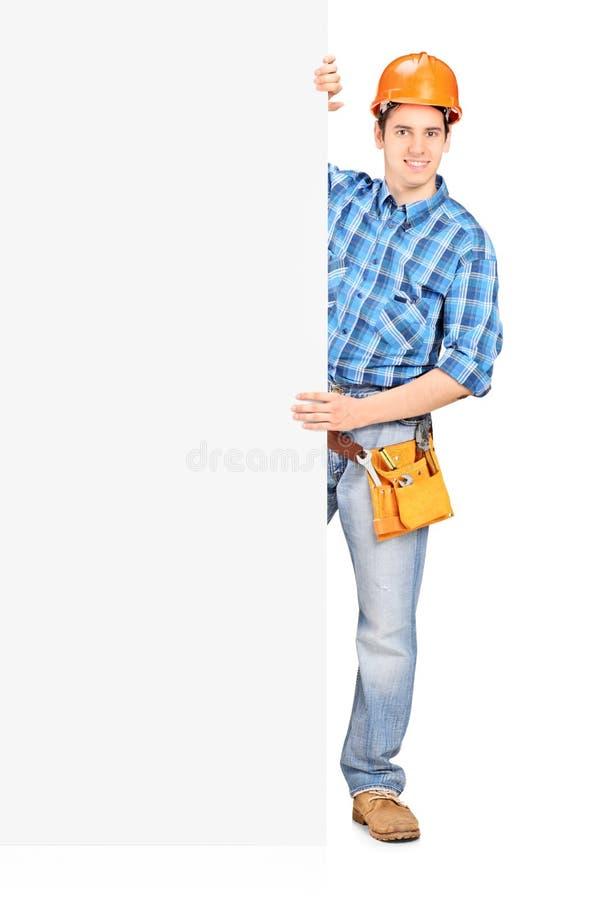 Męski pracownik z hełmem pozuje za panelem zdjęcia stock