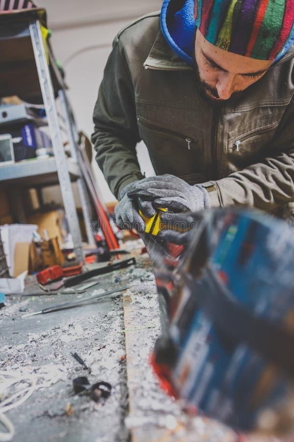 Męski pracownika naprawiania kamień, krawędzi ostrzenie w narty usługa warsztacie, ślizgowa powierzchnia narty ostrzenie obdzierg obraz stock