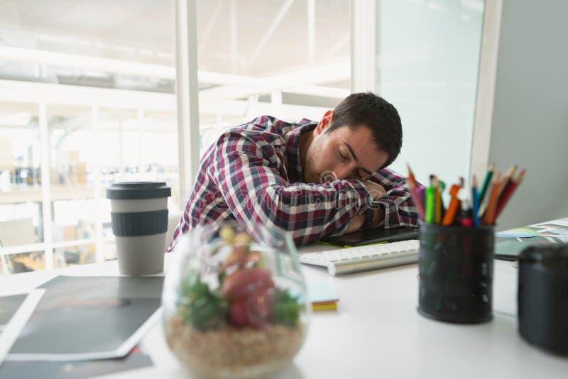 Męski projektant grafik komputerowych dosypianie na biurku w biurze zdjęcia stock
