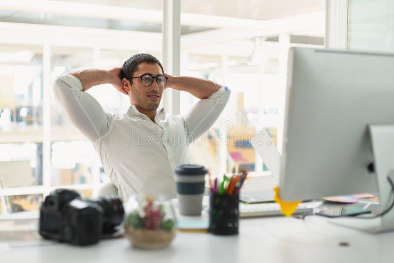 Męski projektant grafik komputerowych obsiadanie z rękami za ręką przy biurkiem zdjęcia stock