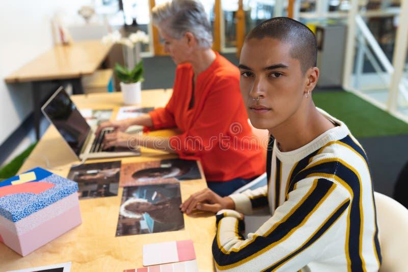 Męski projektant grafik komputerowych patrzeje kamerę podczas gdy coworker używa laptop w tle zdjęcie stock