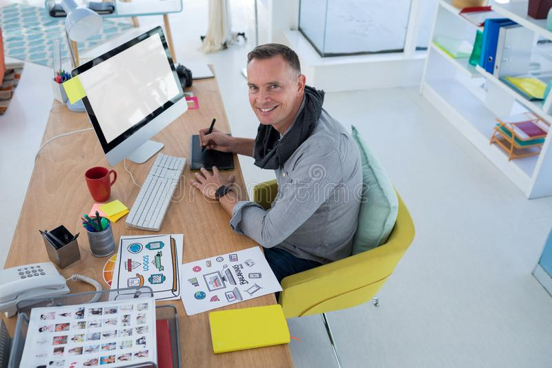 Męski projektant grafik komputerowych pracuje przy biurkiem zdjęcie stock