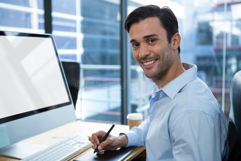 Męski projektant grafik komputerowych używa grafiki pastylkę przy biurkiem fotografia royalty free