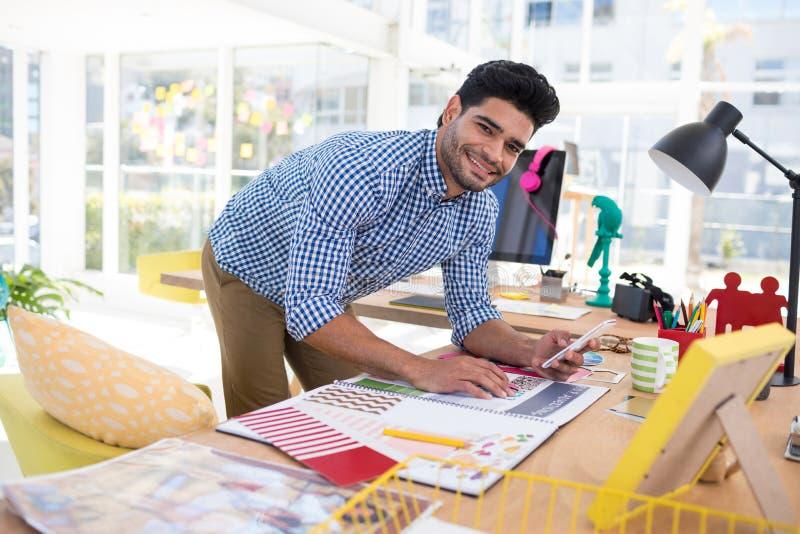 Męski projektant grafik komputerowych używa telefon komórkowego przy biurkiem podczas gdy pracujący fotografia royalty free
