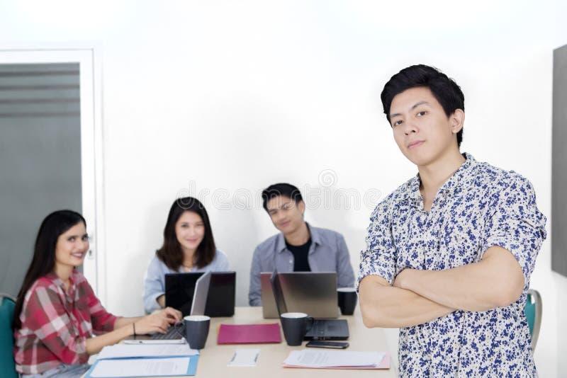 Męski przedsiębiorca patrzeje ufnym z jego drużyną zdjęcia stock