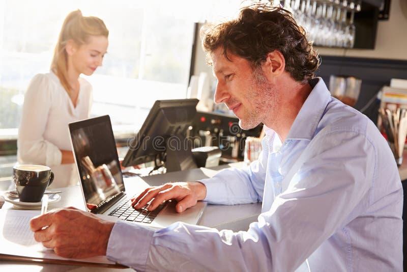 Męski restauracyjny kierownik pracuje na laptopie obrazy stock