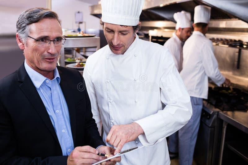 Męski restauracyjny kierownika writing na schowku podczas gdy oddziałający wzajemnie kierowniczy szef kuchni zdjęcia royalty free