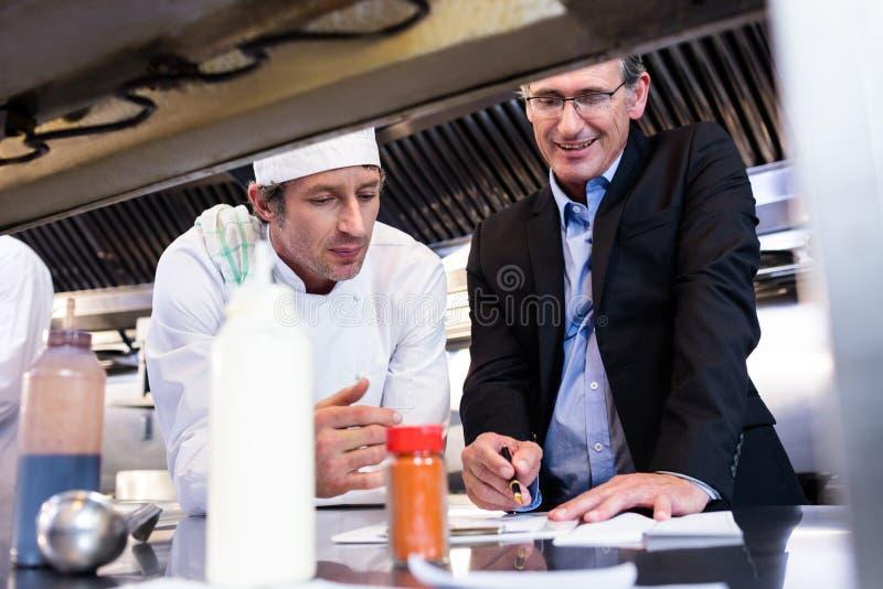 Męski restauracyjny kierownika writing na schowku podczas gdy oddziałający wzajemnie kierowniczy szef kuchni fotografia stock