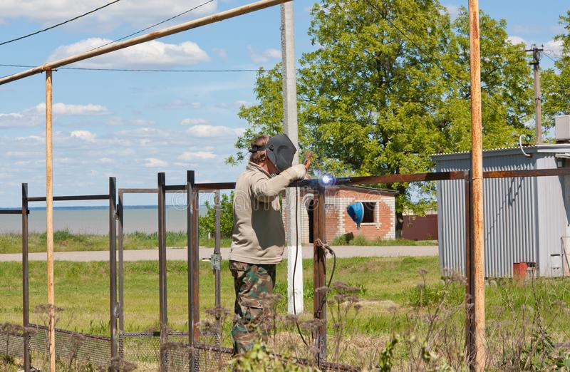 Męski spawacz wspina się ogrodzenie obrazy royalty free