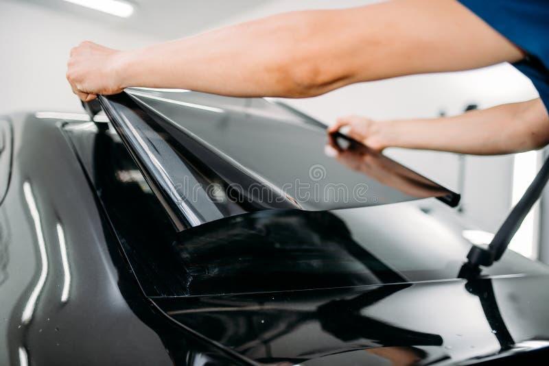 Męski specjalista z samochodowym zabarwia filmem w rękach fotografia royalty free