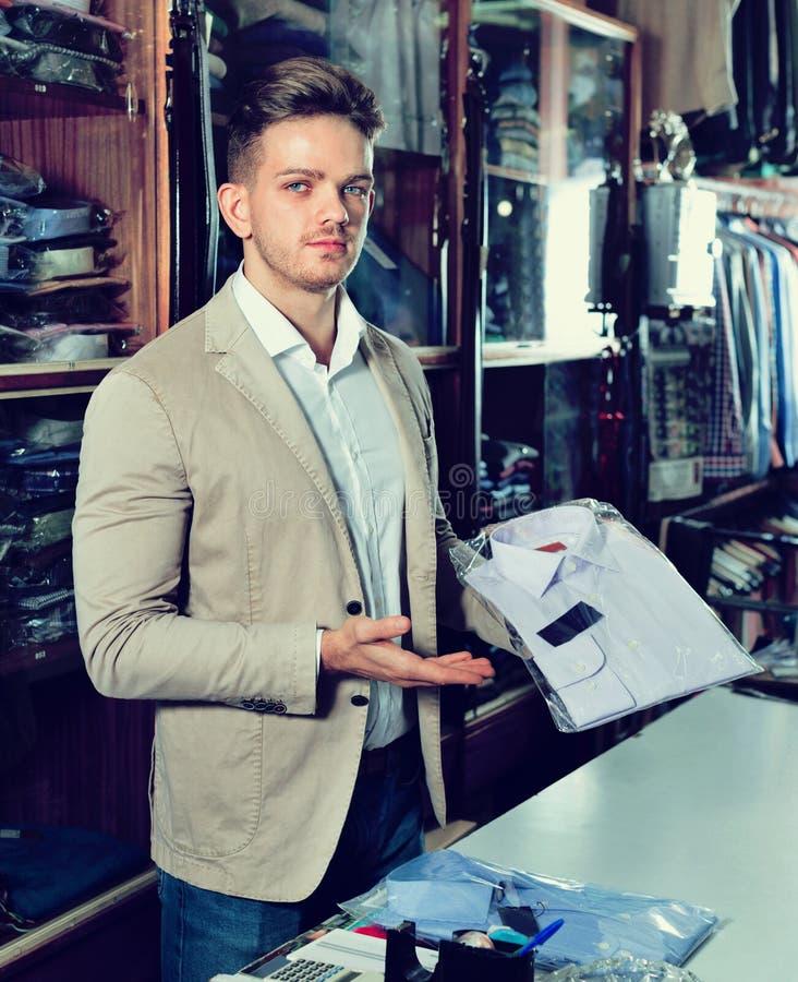 Męski sprzedawca demonstruje koszula w men's płócien sklepie fotografia stock