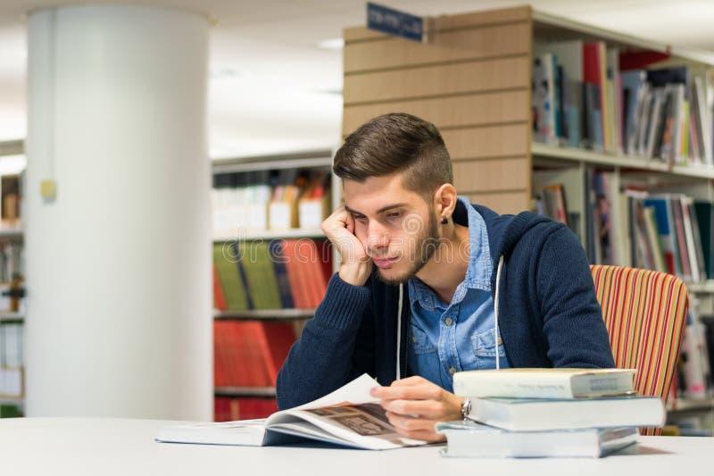 Męski student uniwersytetu w bibliotece zdjęcia stock