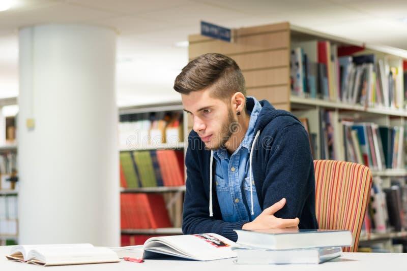 Męski student uniwersytetu w bibliotece zdjęcie royalty free