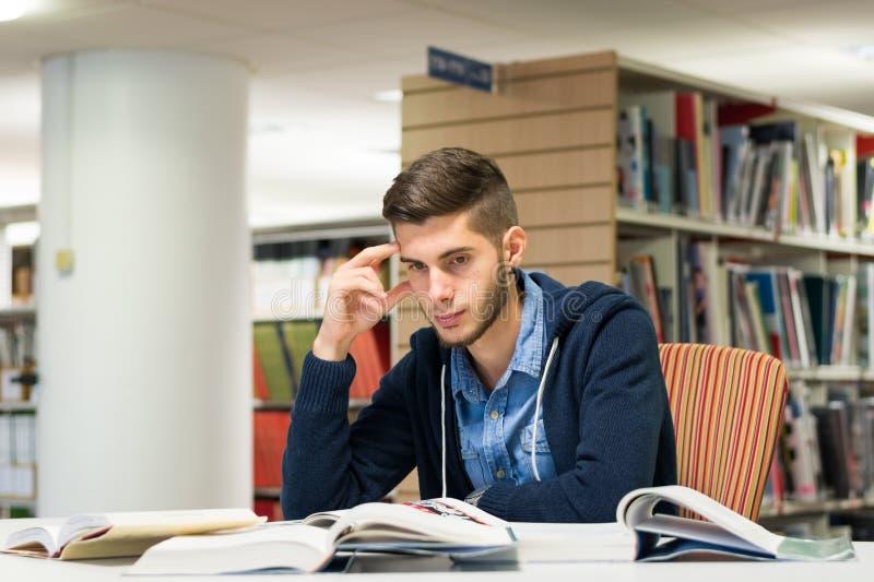 Męski student uniwersytetu w bibliotece obrazy stock