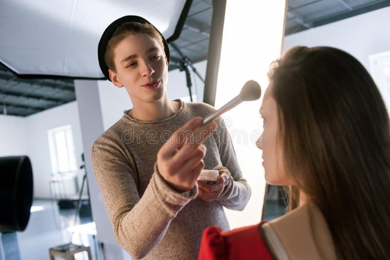 Męski stylista stosuje makeup z proszka muśnięciem obraz royalty free