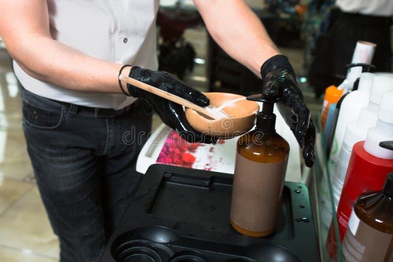 Męski stylista w rękawiczkach przygotowywa kolor śmietankę dla barwiarskiego włosianego zbiornika, maska dla traktowanie procedur zdjęcie stock