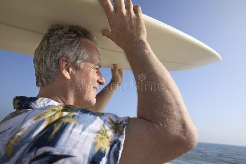 Męski surfingowa przewożenia surfboard przy oceanem zdjęcia royalty free