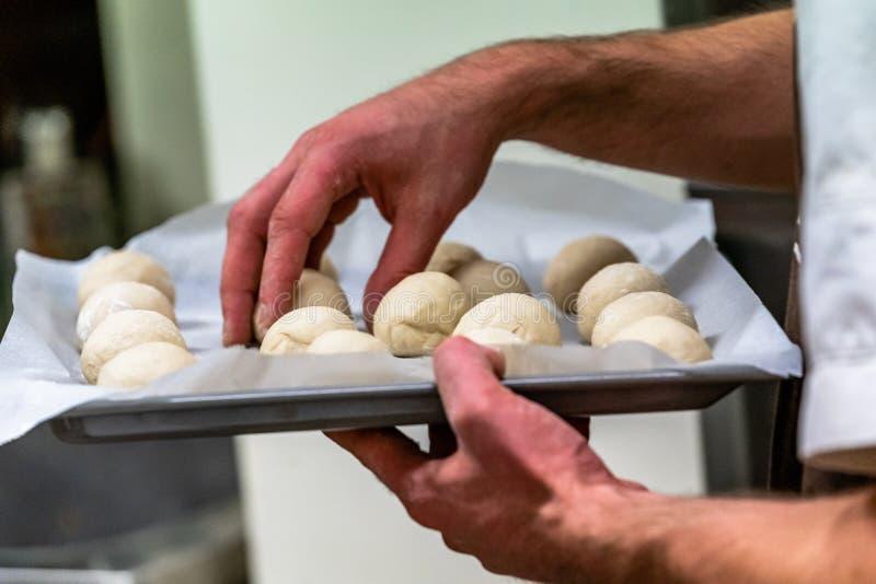 Męski szef kuchni Trzyma nieckę z Małymi Chlebowego ciasta piłkami Umieszczać na C zdjęcie stock