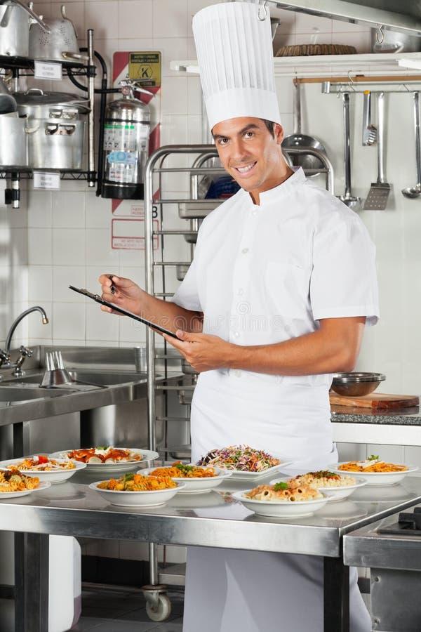 Męski szef kuchni Z schowkiem Przy kuchnią zdjęcia royalty free