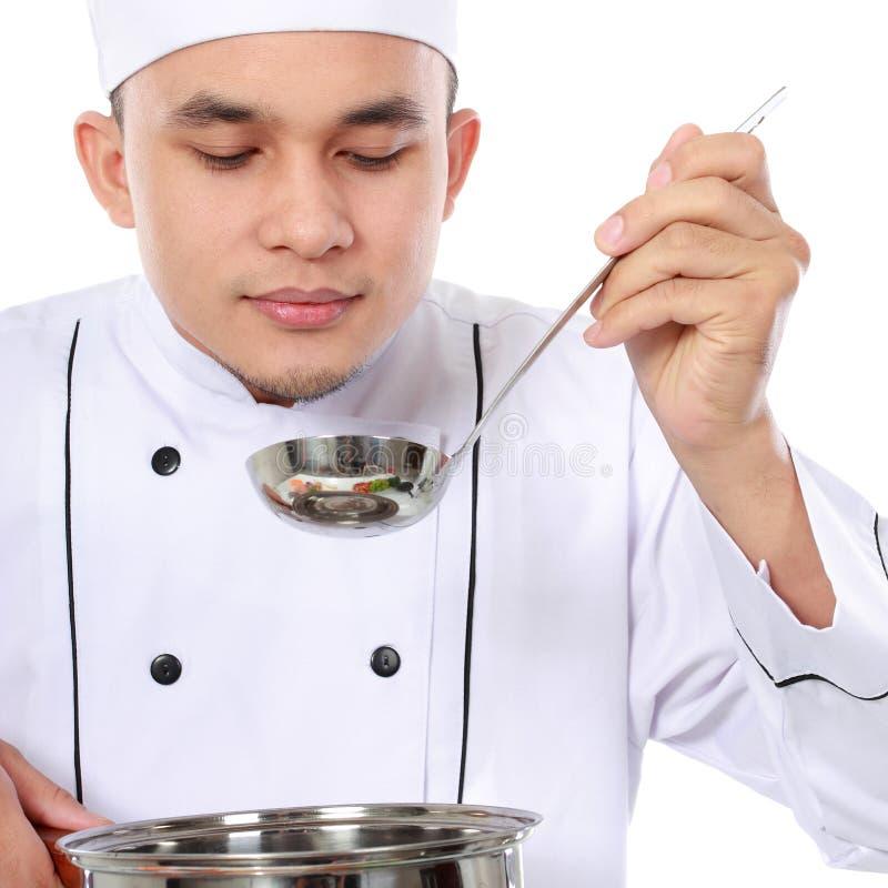 Męski szefa kuchni smak jego kucharstwo zdjęcie royalty free