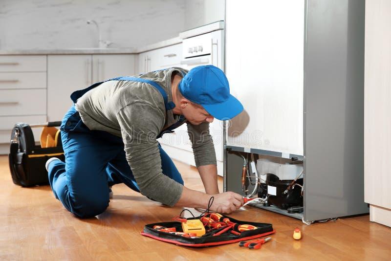 Męski technik w jednolitej naprawianie chłodziarce zdjęcia stock