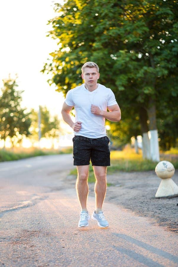 Męski trener biega w hełmofonach Biegacz w ranku w parku Słucha muzyka, ufny spojrzenie Lato zdjęcie royalty free