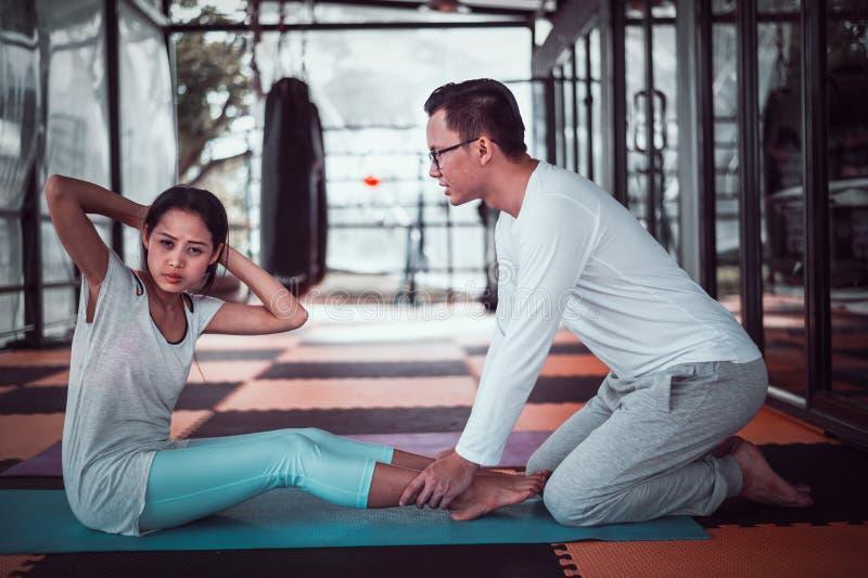 Męski trener podnosi w gym, pojęcie zdrowie pomocy sportsmenka siedzi fotografia royalty free