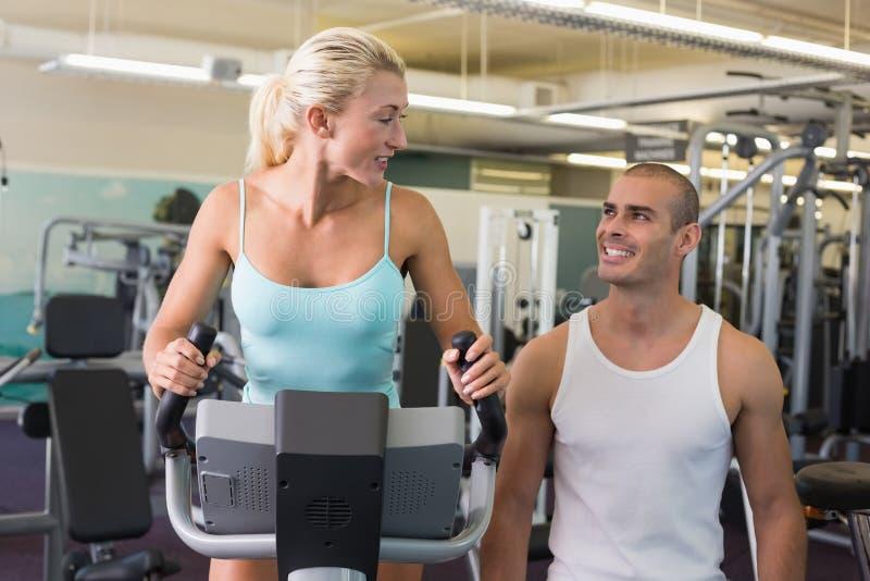 Męski trener pomaga kobiety z ćwiczenie rowerem przy gym zdjęcie royalty free