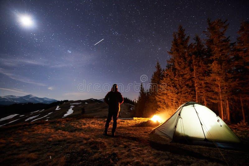 Męski turysta odpoczynek w jego obozie blisko lasu przy nocą pod pięknym nocnym niebem gwiazdy i księżyc pełno fotografia stock