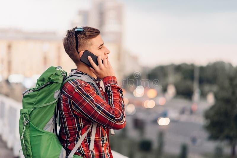 Męski turysta opowiada telefonem z plecakiem zdjęcie royalty free