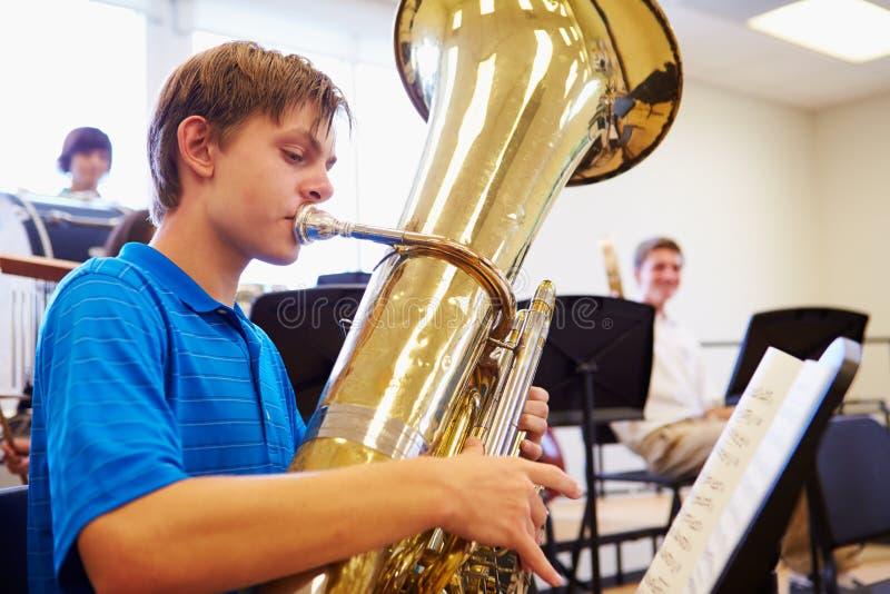 Męski uczeń Bawić się Tuba W szkoły średniej orkiestrze zdjęcie royalty free