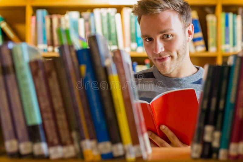 Męski uczeń czyta książkę w bibliotece obraz royalty free